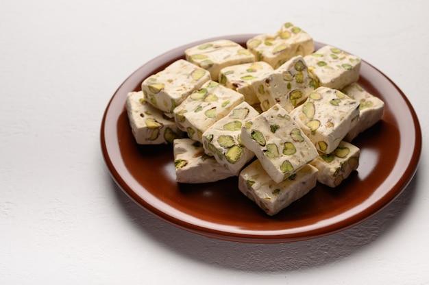 Douceur du nougat arabe oriental aux pistaches sur une plaque en céramique brune sur fond clair.