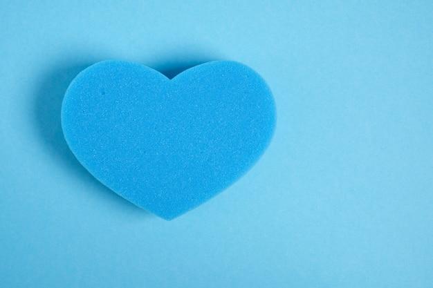 Douche d'éponge en forme de coeur sur la vue de dessus de l'espace de copie de fond bleu