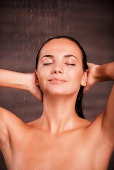 Douche luxueuse. belle jeune femme torse nu debout dans la douche et gardant les yeux fermés