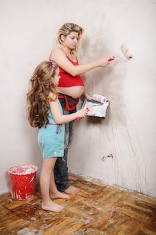 Doughter aide à peindre un mur à la maison avec une mère enceinte