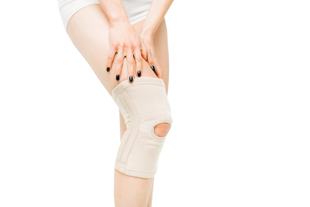 Douleur articulaire, personne de sexe féminin avec bandage à la jambe, douleur au genou sur blanc.