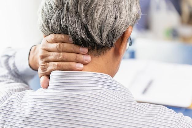 Douleur au cou de l'homme d'âge moyen asiatique en utilisant la main pour masser et frotter la couverture de la main.