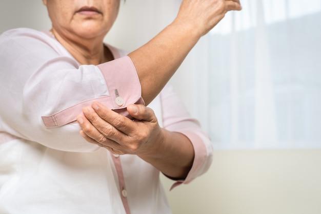Douleur au coude vieille femme souffrant de douleurs au coude à la maison, problème de santé du concept senior