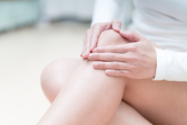 Douleur au genou femmes assises et touche son genou, concept de santé et de médecine