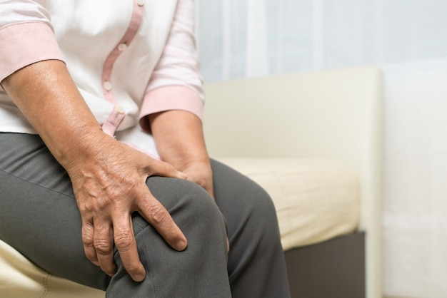 Douleur au genou de la vieille femme à la maison, problème de santé du concept senior