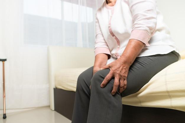 Douleur au genou de vieille femme à la maison, problème de santé du concept senior