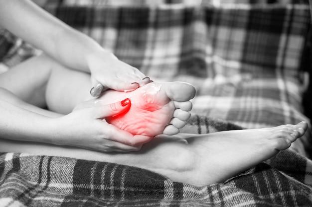 Douleur au pied, fille tient ses mains sur ses pieds, massage des pieds, crampe, spasme musculaire, accent rouge sur le pied, photo noir et blanc, gros plan