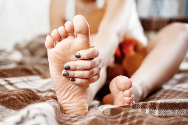 Douleur au pied, la fille tient ses mains sur ses pieds, massage des pieds, crampe, spasme musculaire, gros plan