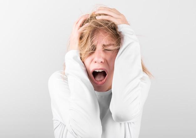 Douleur. belle jeune femme souffrant de maux de tête isolé sur blanc.