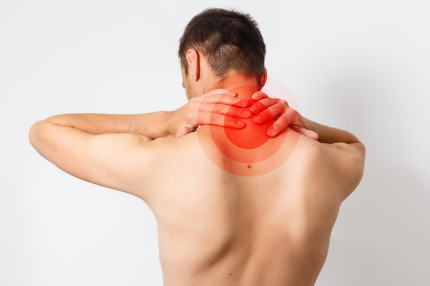 Douleur dans le cou. homme avec mal de dos. corps masculin musclé. isolé sur fond blanc. photo noir et blanc avec point rouge