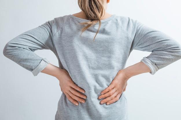Douleur dans les reins. les femmes se tiennent la main dans le dos.