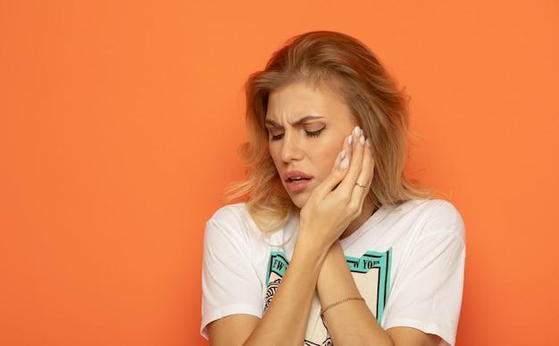 Douleur dentaire et dentisterie. belle jeune femme souffrant de terribles douleurs aux dents fortes. toucher la joue avec la main. femme se sentant mal aux dents douloureux sur fond orange.