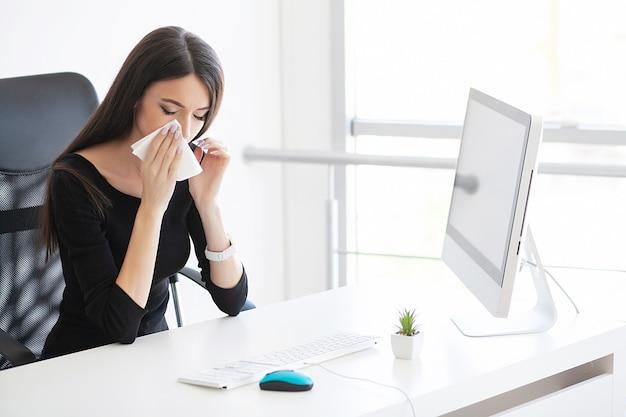 Douleur. femme d'affaires malade souffrant au travail derrière le bureau dans son bureau et ayant un problème d'allergie.