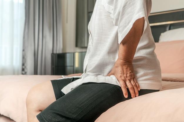 Douleur à la hanche d'une femme âgée à la maison, problème de santé du concept senior