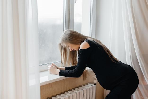 Douleur intense chez une femme enceinte debout près de la fenêtre. grossesse