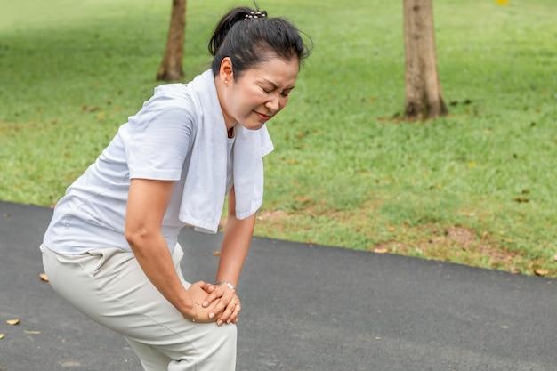 Douleur de jambe asiatique femme senior lors de l'exécution au parc.