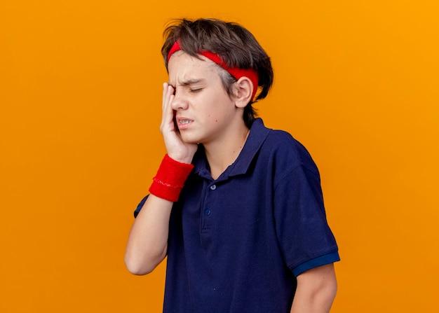 Douleur jeune beau garçon sportif portant un bandeau et des bracelets avec un appareil dentaire en gardant la main sur l'oeil isolé sur un mur orange
