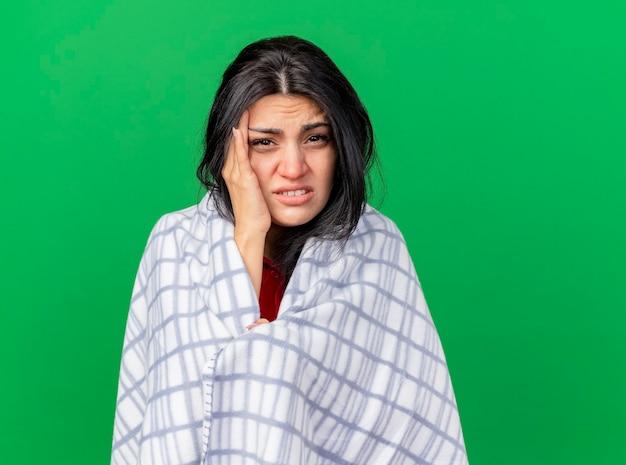 Douleur jeune femme malade enveloppée dans un plaid en gardant la main sur la tête à l'avant ayant mal de tête isolé sur mur vert