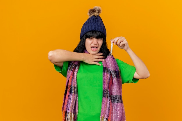 Douleur jeune femme malade portant un chapeau d'hiver et une écharpe tenant et regardant le thermomètre en gardant la main sur la gorge isolé sur un mur orange