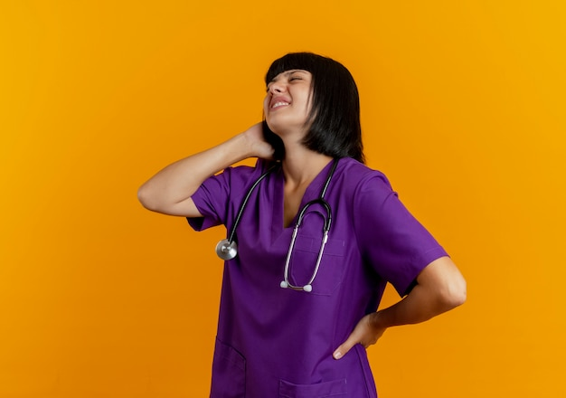 Douleur jeune femme médecin brune en uniforme avec stéthoscope se tient sur le côté tenant le cou derrière