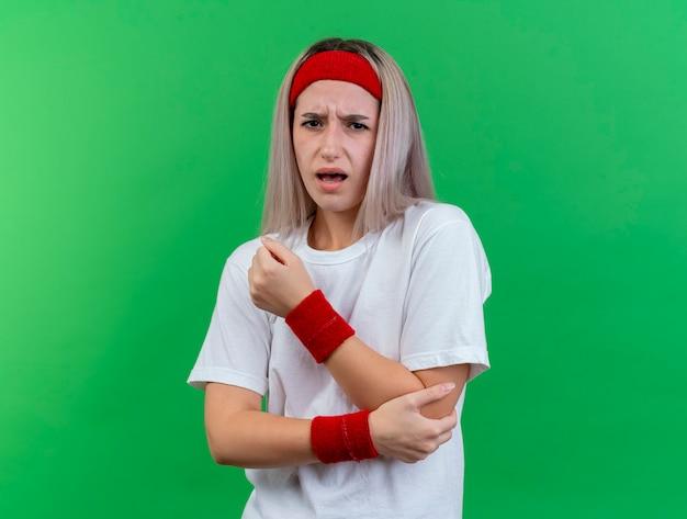 Douleur jeune femme sportive avec des accolades portant bandeau et bracelets tient le coude isolé sur mur vert