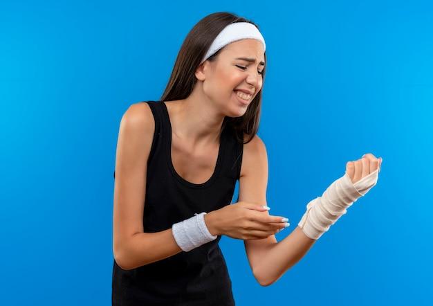 Douleur jeune fille assez sportive portant un bandeau et un bracelet tenant son poignet blessé enveloppé d'un bandage avec les yeux fermés isolé sur le mur bleu