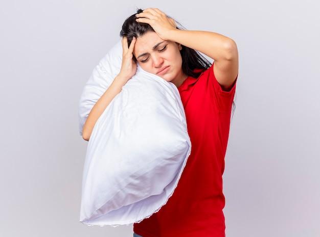 Douleur jeune fille malade caucasienne tenant oreiller et tête avec les yeux fermés isolé sur fond blanc avec espace de copie