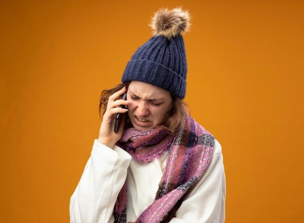 Douleur jeune fille malade portant robe blanche et chapeau d'hiver avec écharpe parle au téléphone isolé sur mur orange