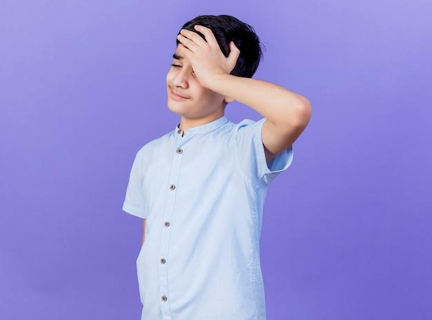 Douleur jeune garçon regardant vers le bas en gardant la main sur la tête ayant mal de tête isolé sur mur violet