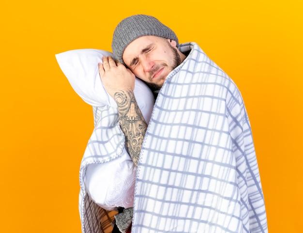 Douleur jeune homme malade portant chapeau d'hiver et écharpe enveloppé dans des prises à carreaux et met la tête sur l'oreiller isolé sur mur orange
