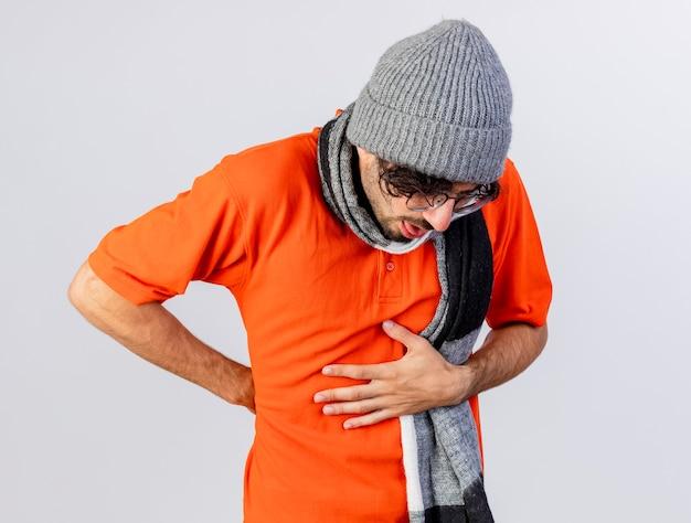 Douleur jeune homme malade portant des lunettes chapeau d'hiver et écharpe mettant les mains sur le ventre et derrière le dos isolé sur mur blanc