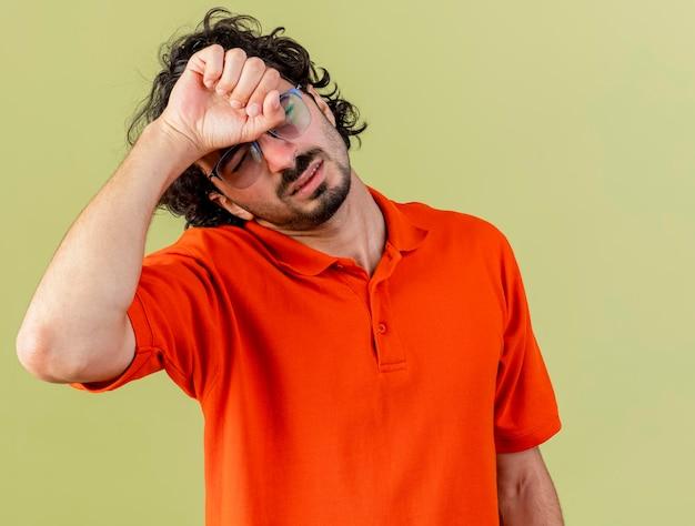 Douleur jeune homme malade portant des lunettes touchant la tête souffrant de maux de tête avec les yeux fermés isolé sur mur vert olive