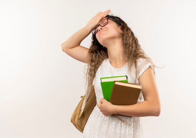 Douleur jeune jolie écolière portant des lunettes et sac à dos tenant des livres mettant la main sur le front avec les yeux fermés isolé sur blanc avec espace copie