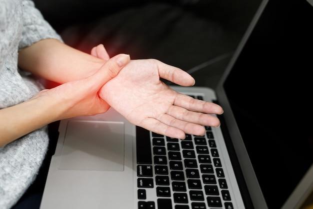 Douleur à la main femmes douleur musculaire tout en travaillant à l'ordinateur