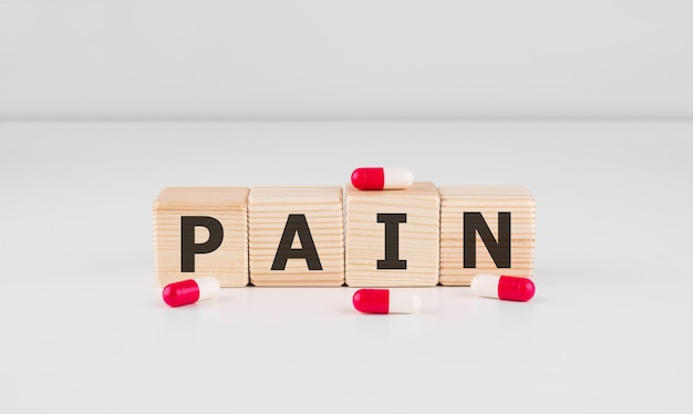 Douleur de mot faite avec des blocs de construction en bois avec des pilules rouges, concept médical.