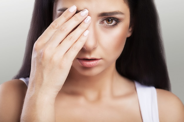 Douleur. le surpoids déprimé est une belle jeune femme aux cheveux noirs qui souffre de graves maux de tête et d'une tête touchante.