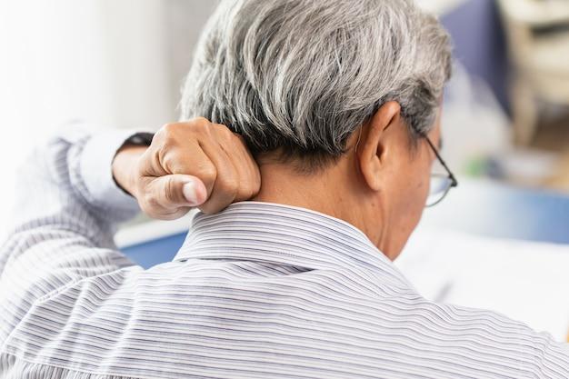 Douleurs cervicales dans le dos de l'aîné asiatique en utilisant la main pour masser et frotter.
