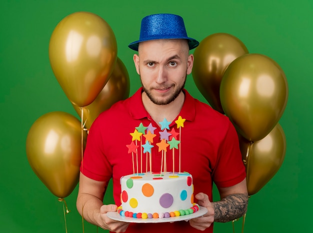 Doute jeune beau mec de fête portant chapeau de fête debout devant des ballons tenant le gâteau d'anniversaire à l'avant isolé sur mur vert