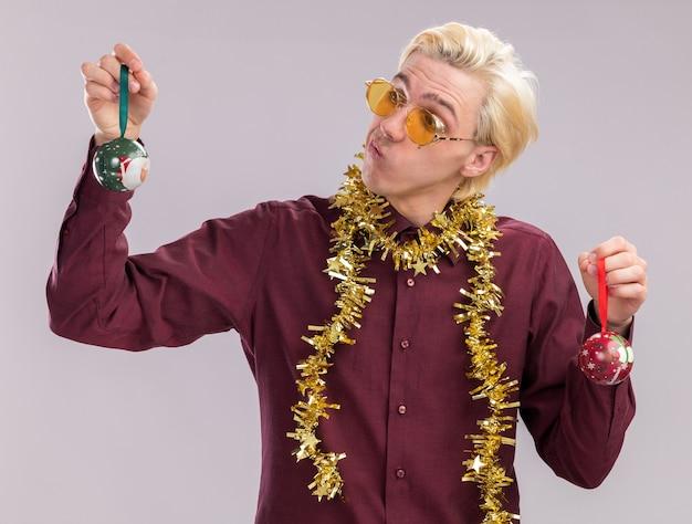 Doute jeune homme blond portant des lunettes avec guirlande de guirlandes autour du cou tenant des boules de noël en regardant un isolé sur un mur blanc