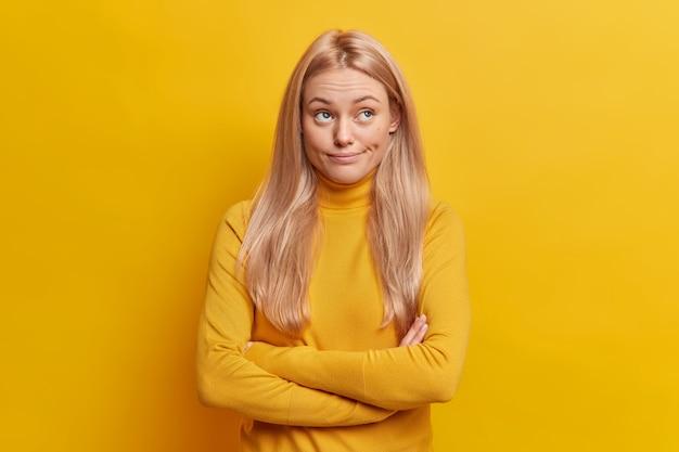 Doute sérieuse jeune femme pensive garde les bras croisés a concentré son expression pense profondément à quelque chose habillé en col roulé décontracté