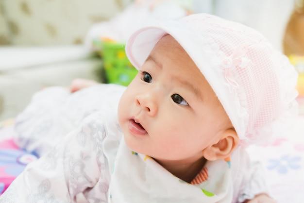Doux bébé asiatique couché sur un lit à la maison avec un dégradé