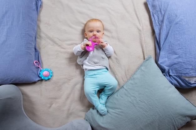 Doux bébé aux cheveux rouges allongé sur une couverture parmi les oreillers