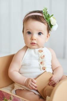 Doux bébé drôle avec chapeau à fleurs. eastercute baby girl 6 months wearing flower hat.