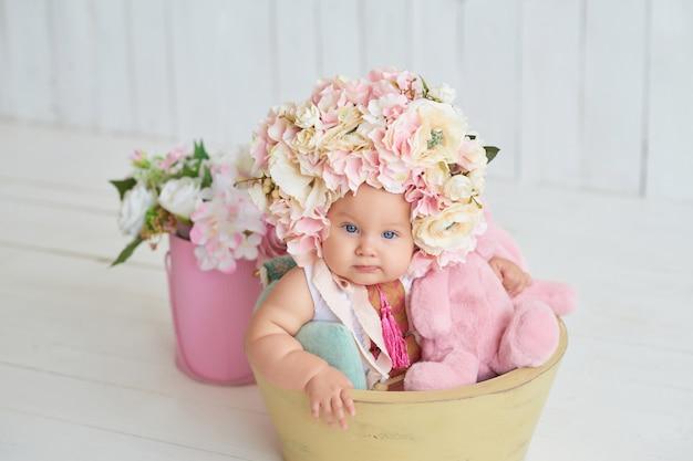 Doux bébé drôle avec chapeau à fleurs. pâques. mignonne petite fille de 6 mois portant un chapeau de fleurs.