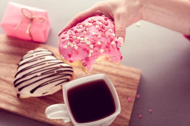 Doux beignet en forme de coeur dans une main avec du café