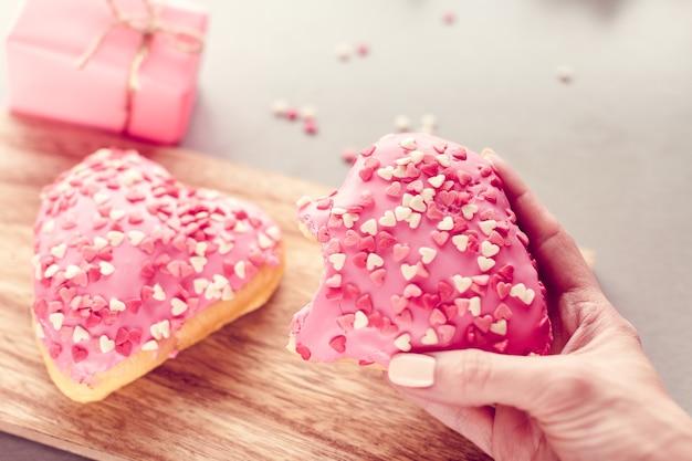 Doux beignet en forme de coeur dans une main