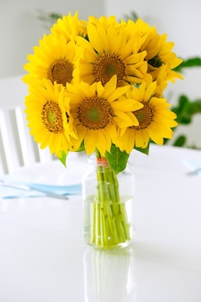 Doux bouquet de tournesols marguerites dans un vase en verre sur une table blanche servi pour le petit-déjeuner ambiance ensoleillée