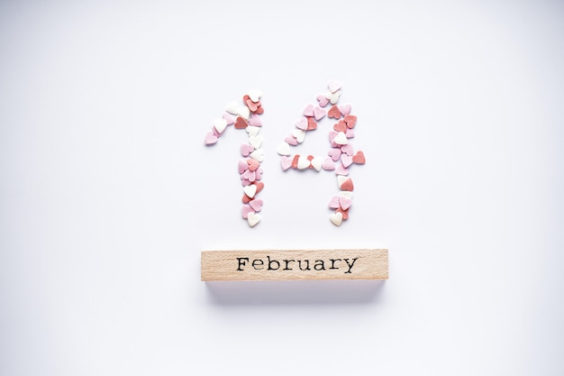 Doux coeurs et calendrier en bois sur fond blanc, mise à plat
