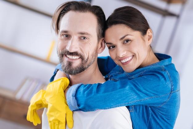 Doux couple agréable souriant et posant sur l'arrière-plan flou