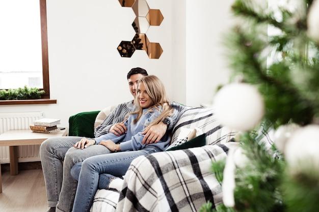 Doux couple embrassant sur un canapé à la maison pendant noël
